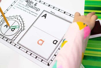 child stamping letters on Christmas Alphabet spin and stamp printable activity
