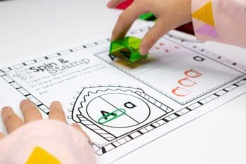preschooler stamping letters on Christmas Alphabet spin and stamp printable game