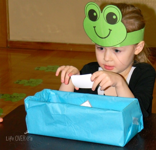 girl wearing frog crown playing frog number line and looking at kindergarten math activity cards