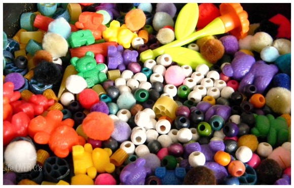 sensory bin of beads, pasta and small objects for fine motor skills