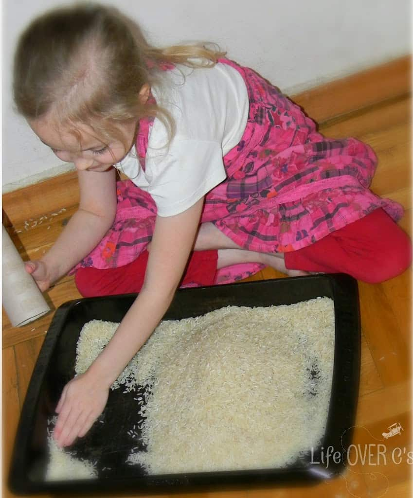 young girl playing with simple rice sensory bin