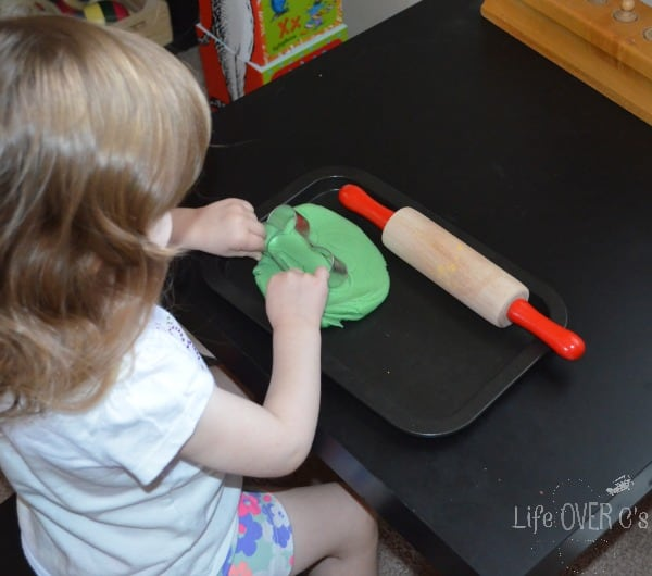 Girl playing with green apple scented play dough