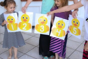 A family holding the Five Little Ducks printable number line sheets.