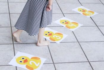 A child hopping on the Five Little Ducks Number Line printable activity.