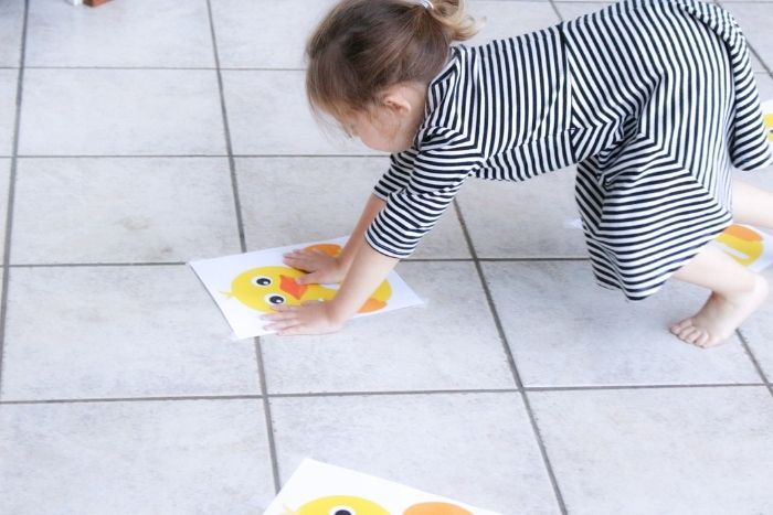 Preschooler hopping on five Little Ducks on the Pond nursery rhyme number line counting to five
