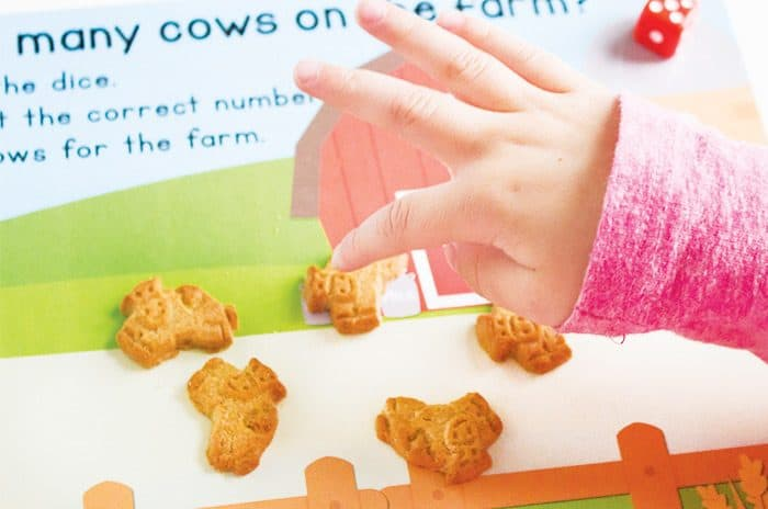 Cows on the Farm Counting game for preschoolers! Kids love it when learning time is also snack time! Kids can count the correct number of cow crackers as they roll the dice.
