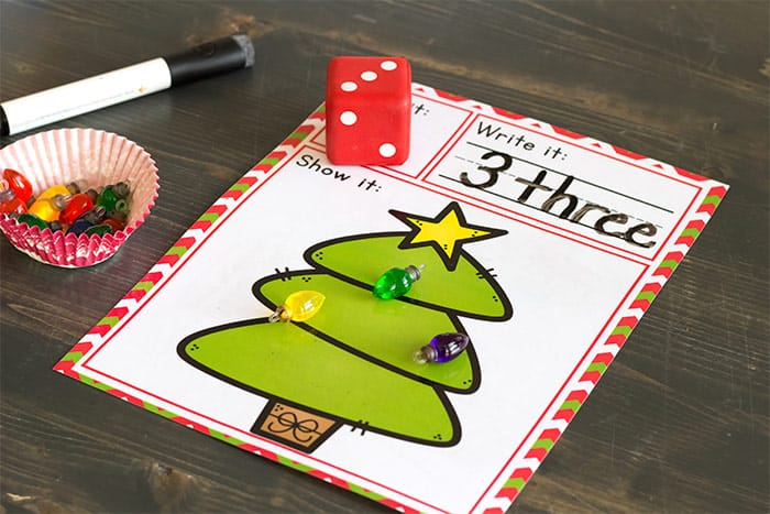 We love Christmas! This simple free printable Christmas Tree roll and count math game for kindergarteners is perfect for Christmas! Kids love rolling the dice, writing the numbers and counting the Christmas lights.