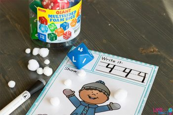 A Snow Themed Roll and Count worksheet with a container of foam dice and a dry eraser marker.