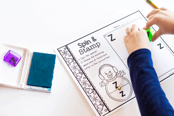 "A child completing the Snowman Spin & Stamp Alphabet Activity worksheet for the letter ""Z""."