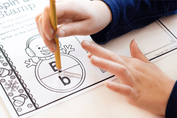 """A child using the """"spinner"""" for the letter """"B"""" Snowman Spin & Stamp Alphabet Activity worksheet."""