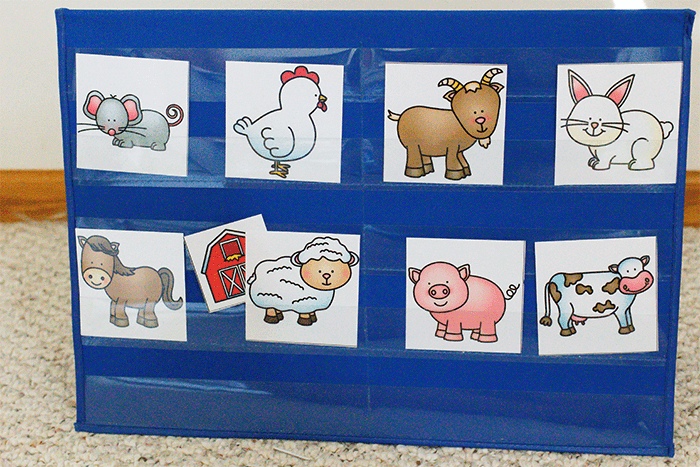 Free printable farm animal game for preschoolers. Pocket chart with farm animal pictures and a barn picture hidden behind a sheep picture for preschoolers to guess the name of the animal.