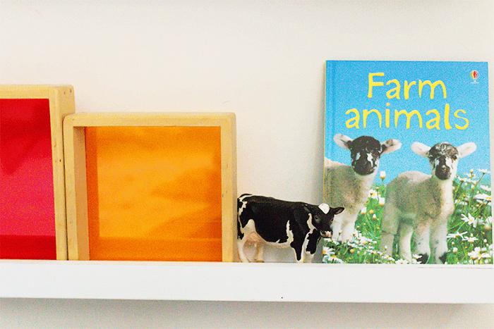 Farm animal book for preschoolers, cow figurine and window block on a shelf in a preschool room.