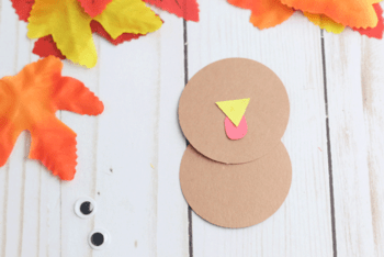 Glue construction paper circles together to create the body of a turkey fall craft for preschool.