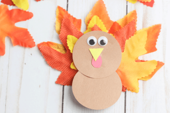 Create a leaf turkey craft for preschool with fake leaves and construction paper.