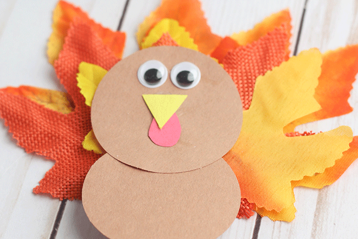 Super simple Thanksgiving leaf turkey craft for preschoolers using construction paper, googly eyes and fake leaves.
