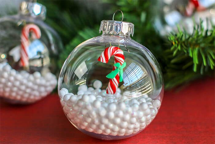 Create a simple Christmas craft with preschoolers. DIY Christmas Ornament with fake snow and miniature candy cane filler for preschoolers to create.