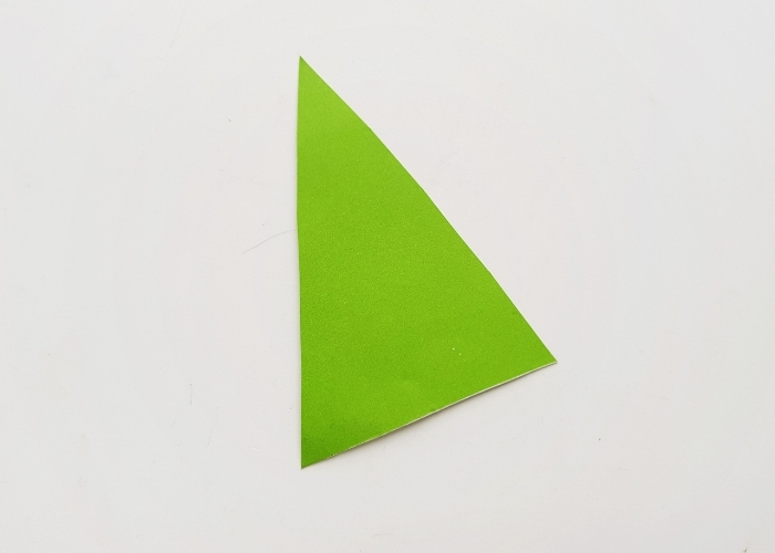 Overhead shot of a green triangle of construction paper for a scrap paper Christmas tree.