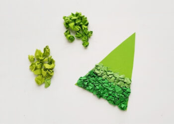 Overhead shot of crumbled construction paper glued to a green triangle for the scrap paper Christmas tree craft.