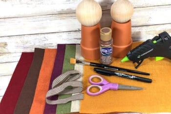 Supplies needed for a fast turkey craft for kids: acrylic paint, felt, scissors, paint brush, ribbon, felt and a glue gun
