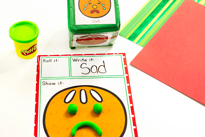 Preschoolers show emotions with play dough on this simple free printable Gingerbread Emotions play dough activity for Christmas preschool theme
