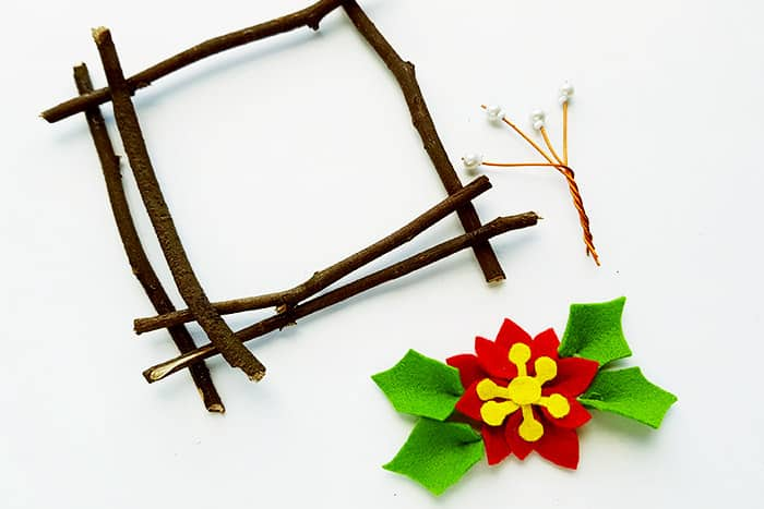 Create a frame with sticks and top with a felt flower to create this natural Christmas craft for kids