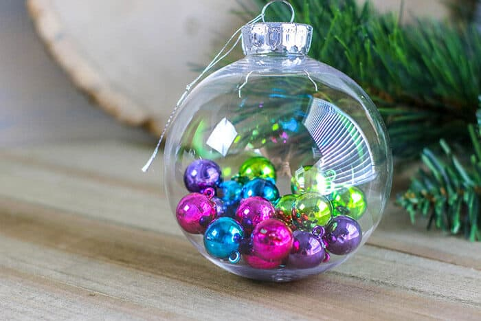 Decorate your Christmas tree with these kid-made Christmas ornaments using clear Christmas ornaments and miniature Christmas ornaments.