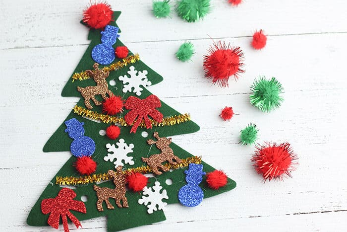 Decorate felt Christmas trees with preschoolers using pom poms, pipe cleaners, and Christmas stickers to create a fun Christmas craft for kids
