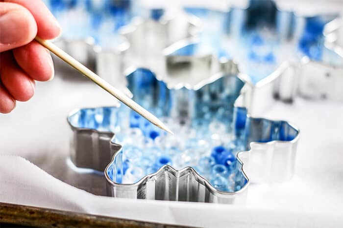 Place cookie cutters on aluminum foil in baking pan. Fill each ornament with a single layer of beads.