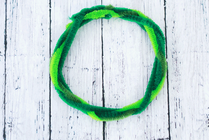 Overhead picture of multiple pipe cleaners of different shades of green wrapped together in a circle.