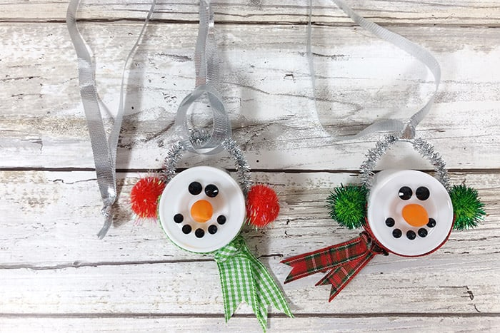 The finished Snowman Tea Light Ornaments on a wood background.
