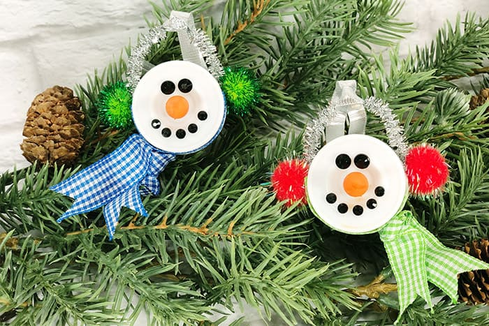 Snowman Tea Light Ornaments hanging on an evergreen branch.