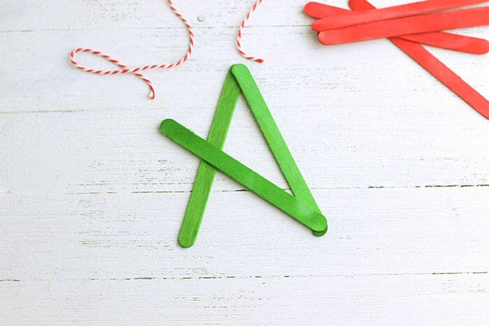 Three green craft sticks glued together to start forming a star for the Star Christmas Ornament Craft.