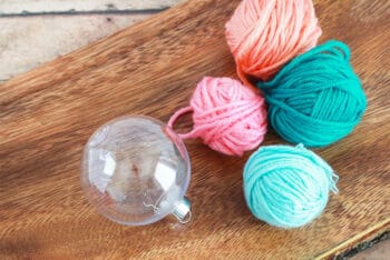 Use yarn scraps of your choice and a clear plastic Christmas ornament to create an easy Christmas ornament craft with your preschoolers