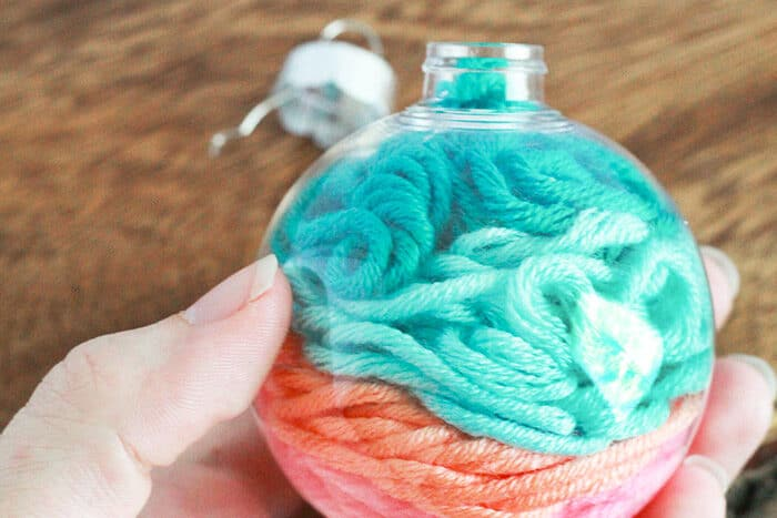 Fill your clear plastic Christmas ornaments with multi-colored yarn for a beautiful DIY Christmas craft for preschool.