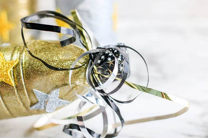 Use curled ribbon to decorate your upcycled plastic bottles for an easy New Year's Eve Noisemaker craft for kids