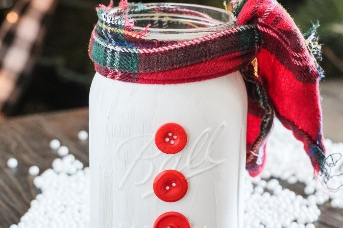 Mason Jar painted like a snowman with red buttons and a plaid scarf.