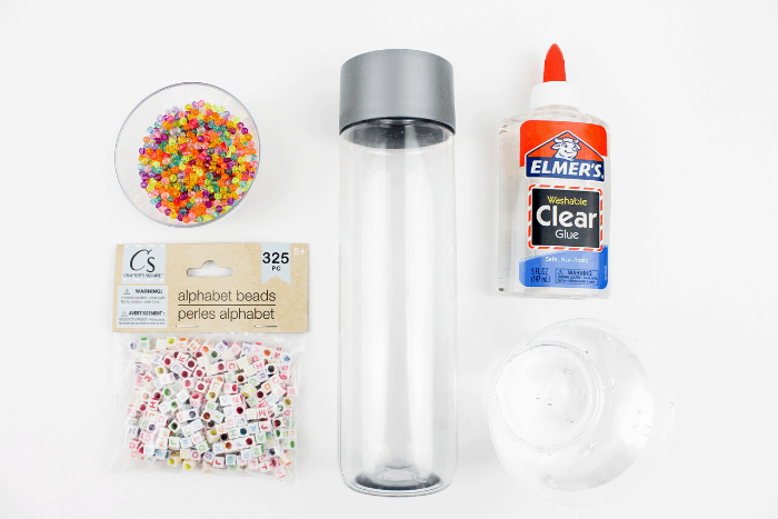 Supplies needed for making a DIY Sensory Bottle. Rainbow beads, alphabet beads, clear water bottle, Clear Elmer's Glue, and water.