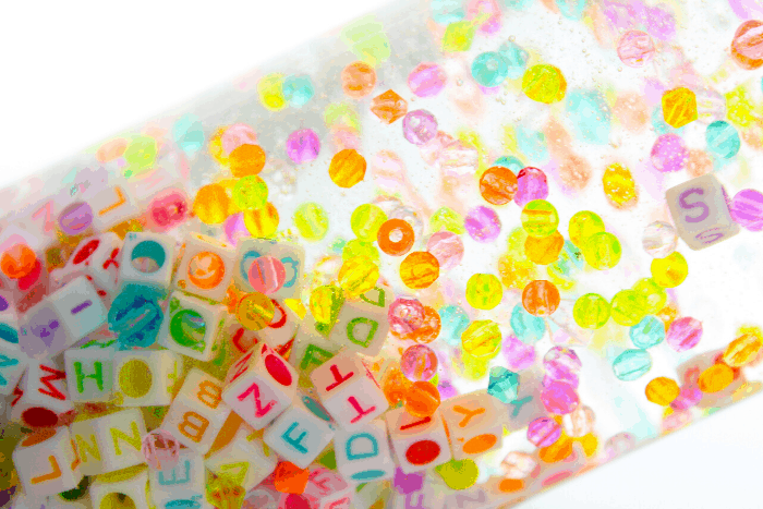 Rainbow colored round beads and alphabet beads in a clear bottle with liquid.