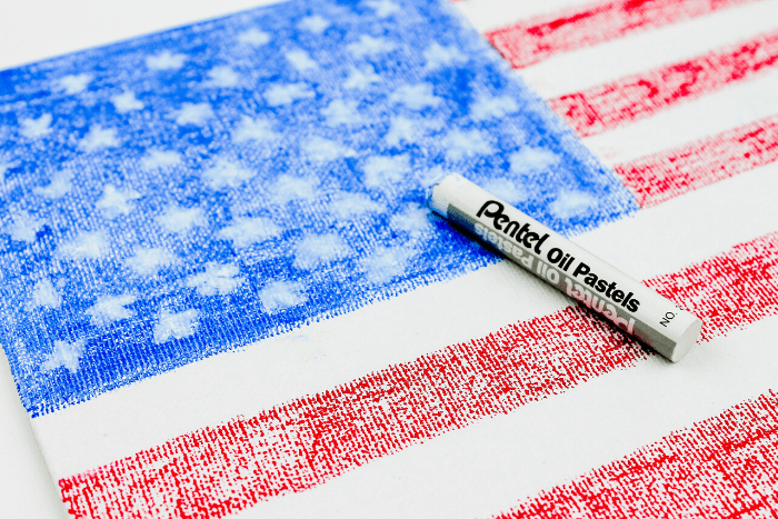 White pastel crayon on top of a completed us flag craft for kids.
