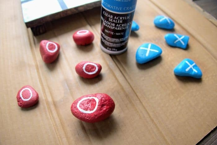 DIY Rock Tic Tac Toe rocks painted blue and red with x and o on them.