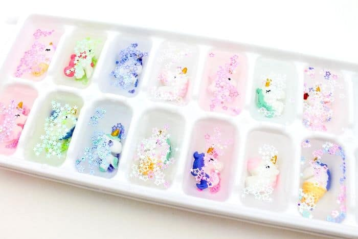 Mini Unicorn head figures in an ice cube tray with water and glitter.