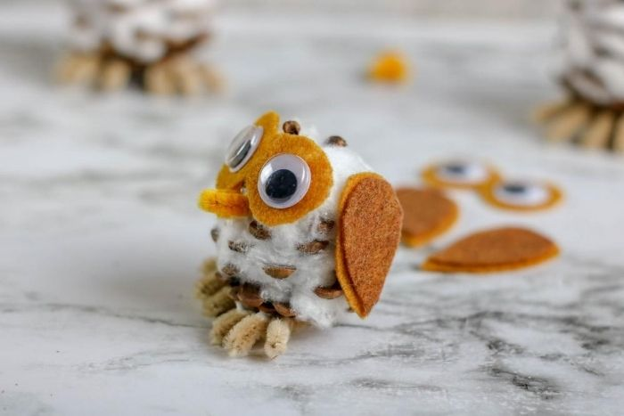 A pinecone owl craft from the side.
