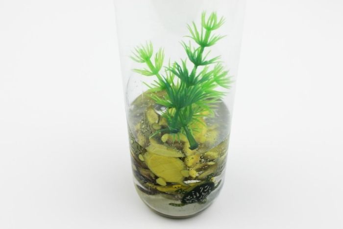 Small turtle toys in clear school glue with artificial greenery in a clear bottle.