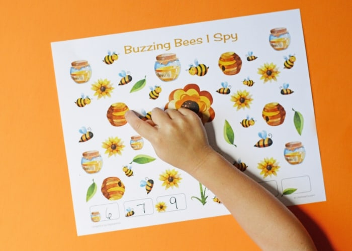 Child's hand pointing to a bee hive on a bee-themed i-spy sheet.