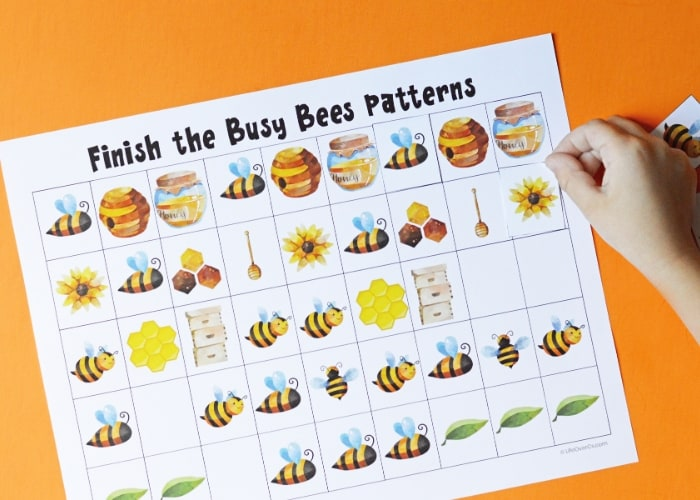 Hand finishing up a bee-themed pattern worksheet.