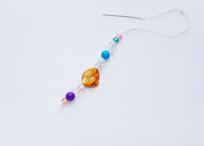 Colorful beads strung onto a thread with a needle.