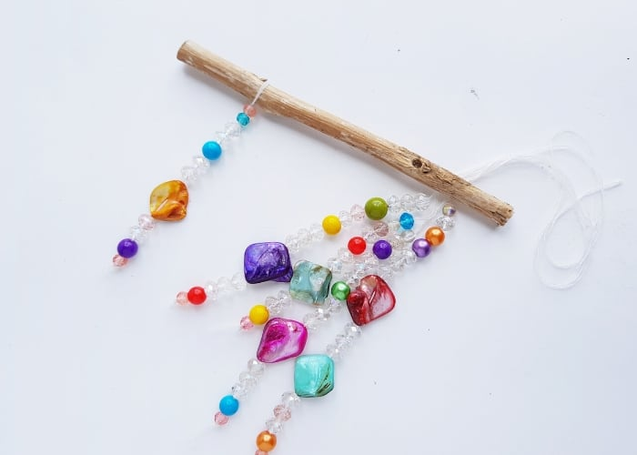 Colorful beads on strings being attached to a stick to make a suncatcher.
