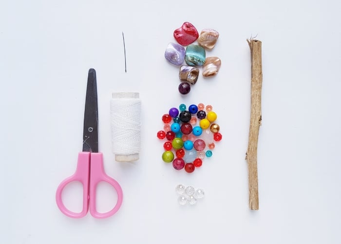 Supplies for making a DIY Suncatcher for kids. Scissors, white thread, a sewing needle, colorful beads, and a stick.