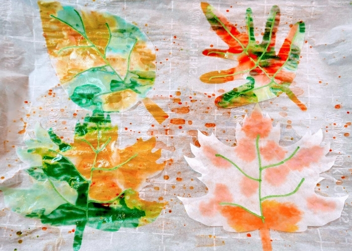 Using dye to decorate leaves cut from coffee filters.