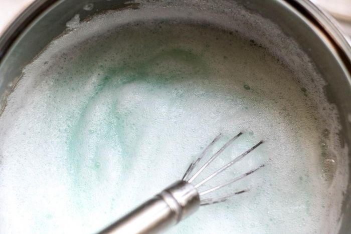 a metal whisk in a stainless steel bowl mixing a foaming blue mixture.
